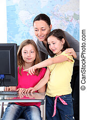 Teacher with kids in front of desktop computer