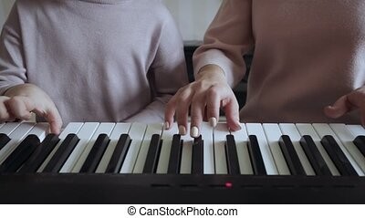 Teacher with little girl playing on the electric piano.