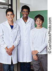 Teacher With Male Students Standing Together In Science Lab