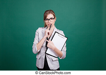 teacher with papers in green boards