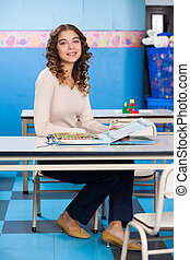 Teacher With Popup Book Sitting At Desk In Preschool