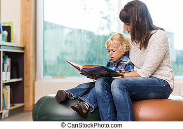 Teacher With Schoolboy Reading Book