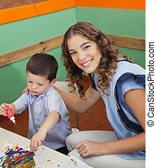 Teacher With Student Painting In Classroom