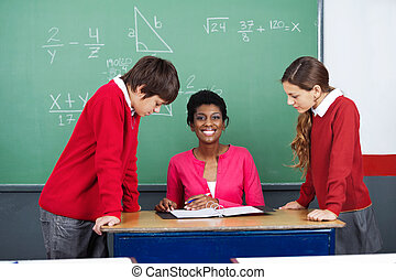 Teacher With Students At Desk