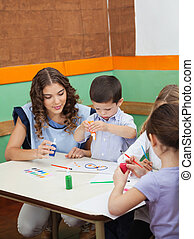 Teacher With Students Painting At Desk
