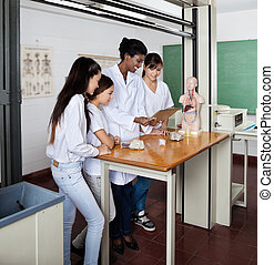 Teacher With Students Using Digital Tablet In Science Lab