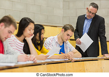 Teacher with students writing notes in lecture hall