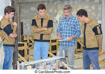 Teacher with three students in practical class