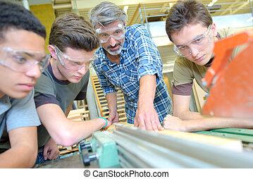 Teacher with three students,  using machine