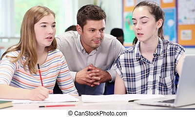 Teacher With Two Female High School Students Working At...