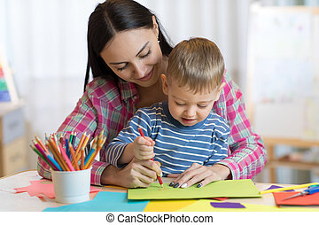 teacher woman drawing with child boy in classroom