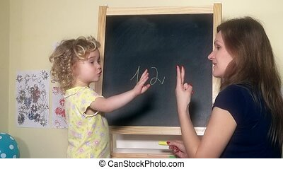 Teacher woman writing numbers on chalk black board for...