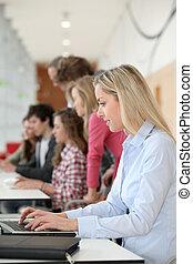 teacher working on laptop computer in classroom
