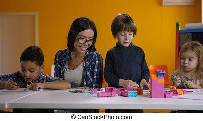 Teacher working with children in preschool class