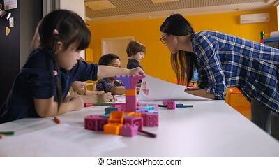 Teacher working with creative kids in kindergarten