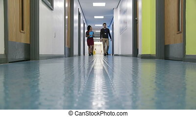 Teachers In The Corridor - Male and female teacher are...