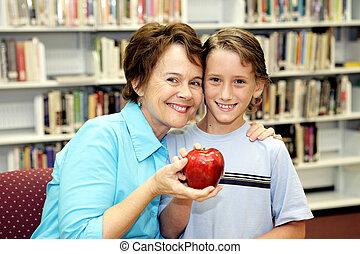 Teachers Pet - A cute school boy giving his teacher an apple...