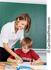 Teaching at school - Young teacher showing the student how ...