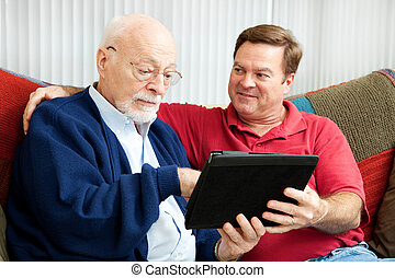Teaching Dad to Use Tablet PC - Adult son teaching his...