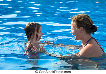 Teaching daughter how to swimm - Mother teaching her ...