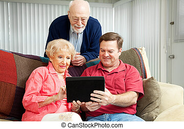Adult son teaching his parents to use their new tablet pc.
