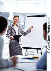 Teaching - Smart businesswoman standing by whiteboard and...