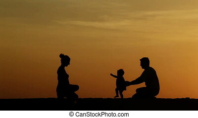 Teaching to walk - Silhouette of parents teaching their...