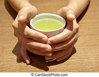 Teacup - Woman hands holding Japanese green teacup on table.