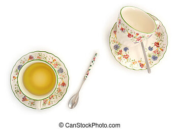 Pretty springtime teacups in flat lay on white background. Vertical format in natural light.