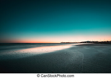 Teal and orange view of winter beach sunset.
