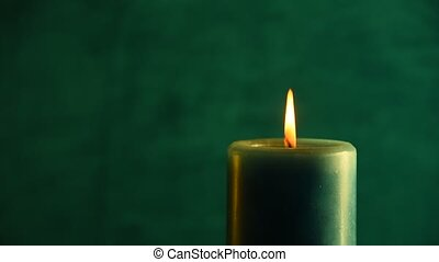 Teal candle trembling flame out of