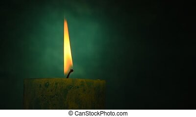Teal candle trembling flame close up out of the dark blue green background, off-center, blown out