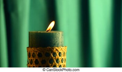 Teal candle trembling flame with green curtain background and blown out