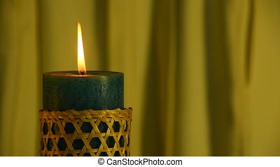 Teal candle trembling flame with yellow curtain background...