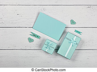 Teal gift boxes and paper note on white table