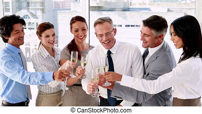 Business team celebrating with champagne in the office