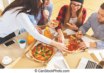Team eating pizza at workplace