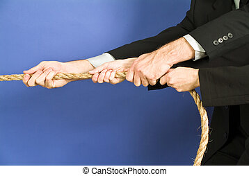 Team effort - concept photo of business people using a rope...