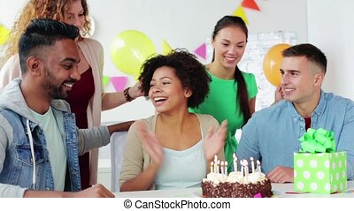 team greeting colleague at office birthday party