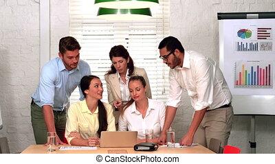 Team having a meeting using laptop