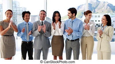 Business team standing in a row clapping at camera in the office