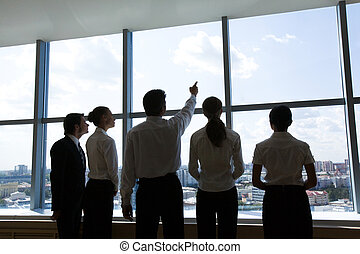 Team leader - Rear view of business group standing in row...