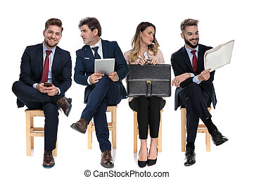 4 businessmen holding, phone, table, newspaper and briefcase