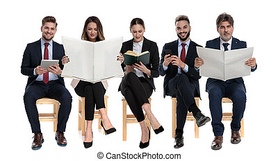 5 businessmen reading from book, newspapers, tablet and phone
