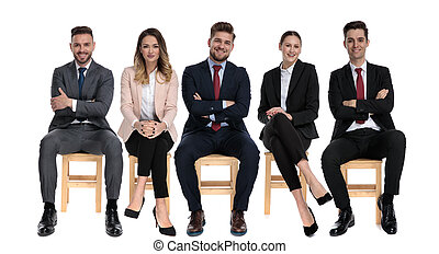 Team of 5 positive businessmen smiling while sitting