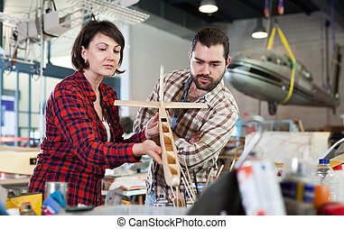 Team of aircraft enthusiasts working in workshop