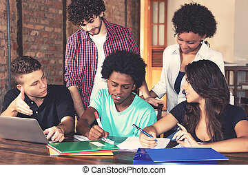 Team of american students learning together for exam at...