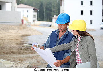 Team of architects checking plans on site
