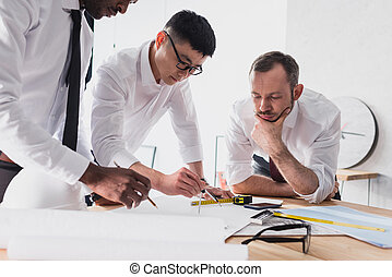team of architects working on plan together in modern office