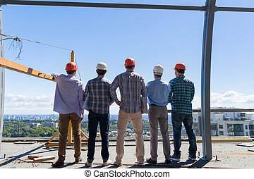Team Of Builders On Costruction Site Back Rear View, Foreman Group In Hardhat Outdoors Partnership And Teamwork Concept